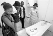 BOUBLE HEARBREAK: Nobuhle Ndlebe, left, broke down after seeing her baby's decomposed body. With her are Sivuyile Ndlebe and Salome Ledwaba. Pic. Veli Nhlapo. 30/01/2007. © Sowetan