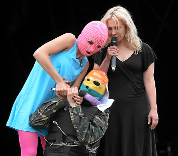 Pussy Riot members Nadya Tolokonnikova (masked) and Maria Alyokhina perform at the Glastonbury Festival in 2015. The man in the mask is meant to be Vladimir Putin.