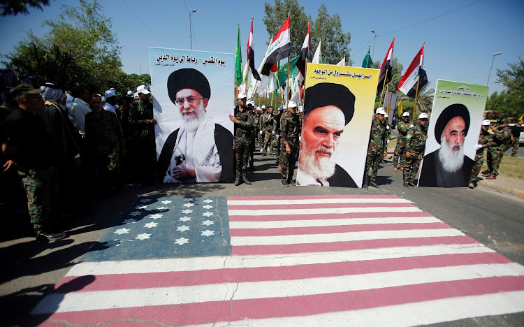 Iraqi Shi'ite Muslims hold portraits of Iran's late leader Ayatollah Ruhollah Khomeini (C), Supreme Leader Ayatollah Ali Khamenei (L) and Iraq's top Shi'ite cleric Grand Ayatollah Ali al-Sistani during a parade marking the annual al-Quds Day.