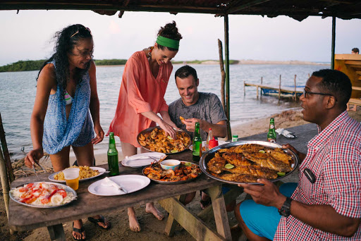DR-Travelers-Sharing-Meal-2.jpg - Dine on local cuisine in the Dominican Republic.