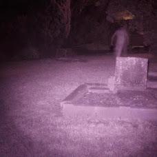 Fantasma detrás de una lápida en el cementerio