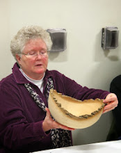 "Photo: Margaret looks at the bowl shape and told Duane that he could put it back on the lathe and take a little off the bottom to ""lift it up"" a little."