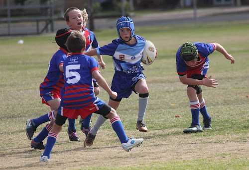 Campbell Williams fends off several Gunnedah defenders in the under-9s match.