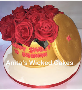 A gold hat box shaped cake with roses