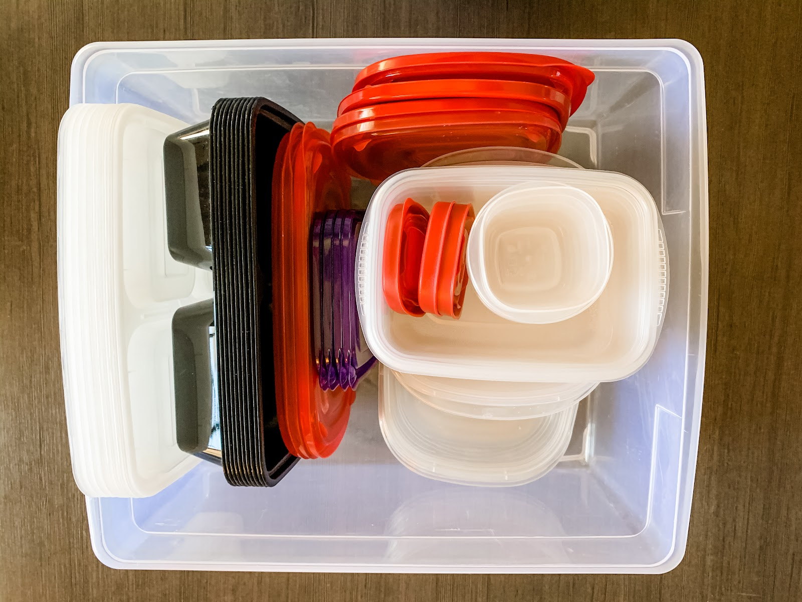 Simple example of how to organize food storage containers. Like sizes are stacked together inside of a plastic sweater bin. Lids are grouped together by size and shape.