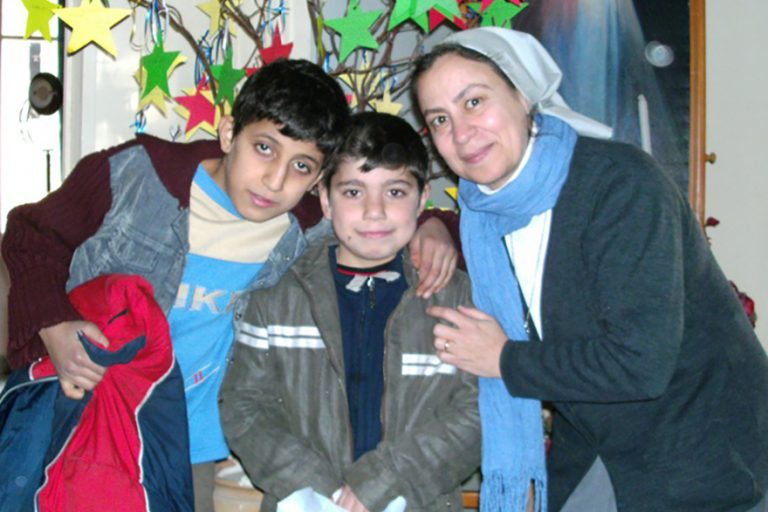 Sister Annie Demerjian and children with anoraks © Aid to the Church in Need