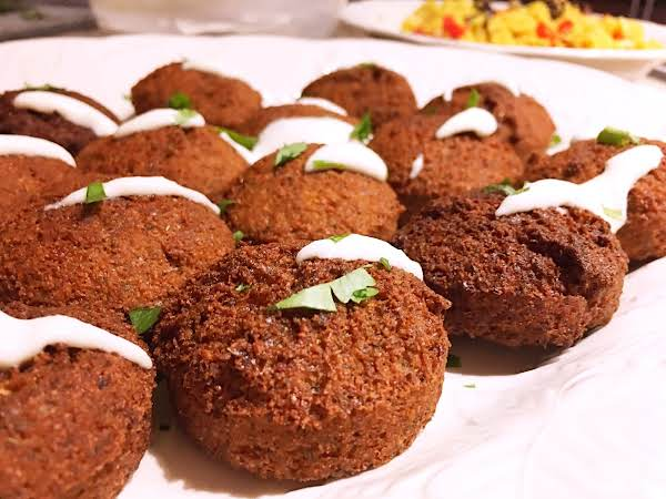 Falafels With Yogurt Sauce On Top On A White Plate With Couscous In The Background.