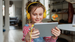 image of young girl with headphones looking at tablet