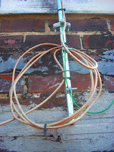 Photo: A metal antenna mast grounded with 12awg copper wire and a screw clamp.