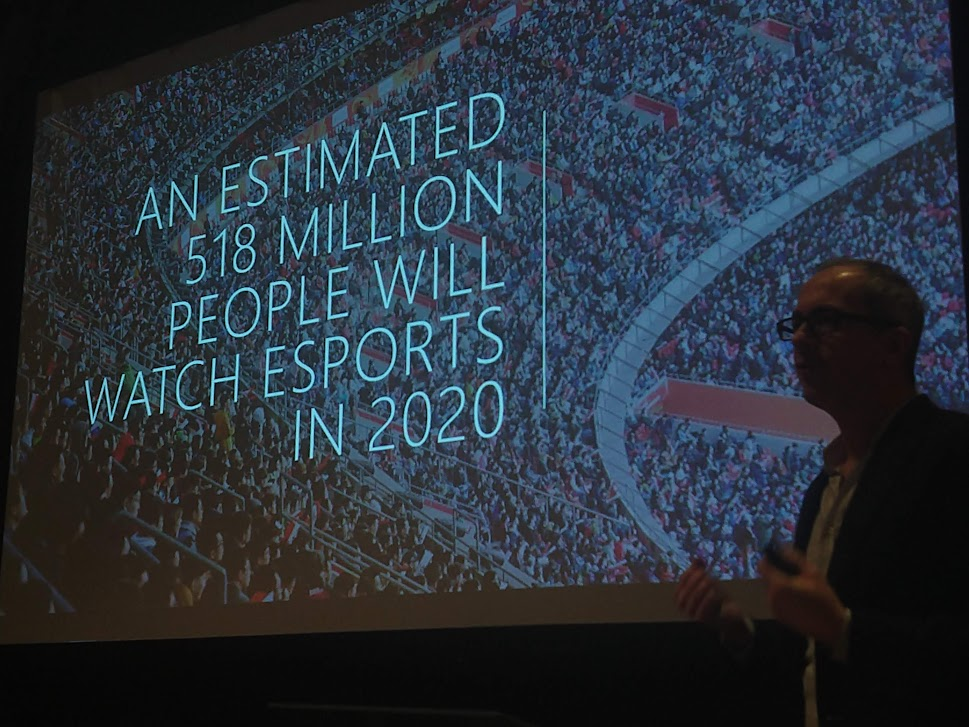 Presenter speaking about esports. Slide of a stadium with the words: An estimated 518 million people will watch esports in 2020.