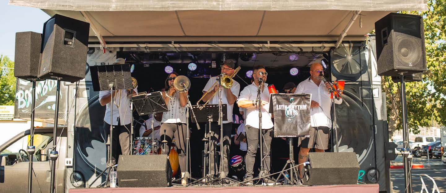 Seven people playing musical instruments on a stage.
