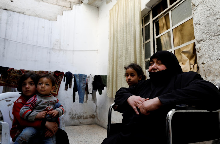 Seham Hamu, a grandmother, sits on a wheelchair next to her grandchildren in Douma, in the eastern suburbs of Damascus, Syria, on March 9 2021. Picture: REUTERS/OMAR SANADIKI