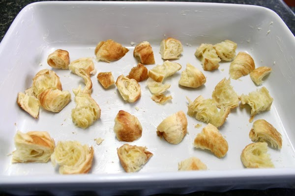 Torn up pieces of bread in a white baking dish.