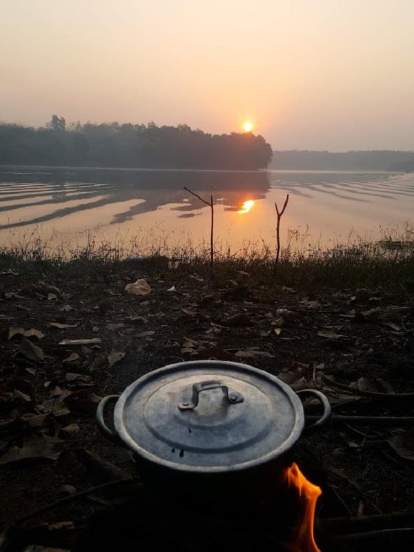 Anh Hà nấu đồ ăn bên sông ở Bình Phước (Ảnh: Thanh Niên)