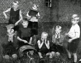 Photo: Muzikanten v.l..n.r. Boven: Jans Oosting op een blauw drinkenkannegie, Job Boelens op een rollegiesblik van Vegter? Onder: Marchienus Jobing op mondharp, Henk Sloots op de grote trom, vers oet de brandkoel haold!!, Jan Oosting ok op mondharp, Geert Hoving op traachter (trechter) en Jannes Boelens als dirigent. Henk Sloots was net deur een iem (bij) stoken, vlak bij 't oog, mor kun toch optreden. Foto gemaakt in ± 1949 door Berend Oosting