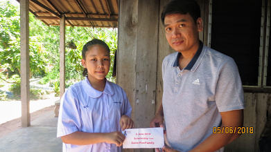 Photo: Kancharna (11) recieves her scholarship