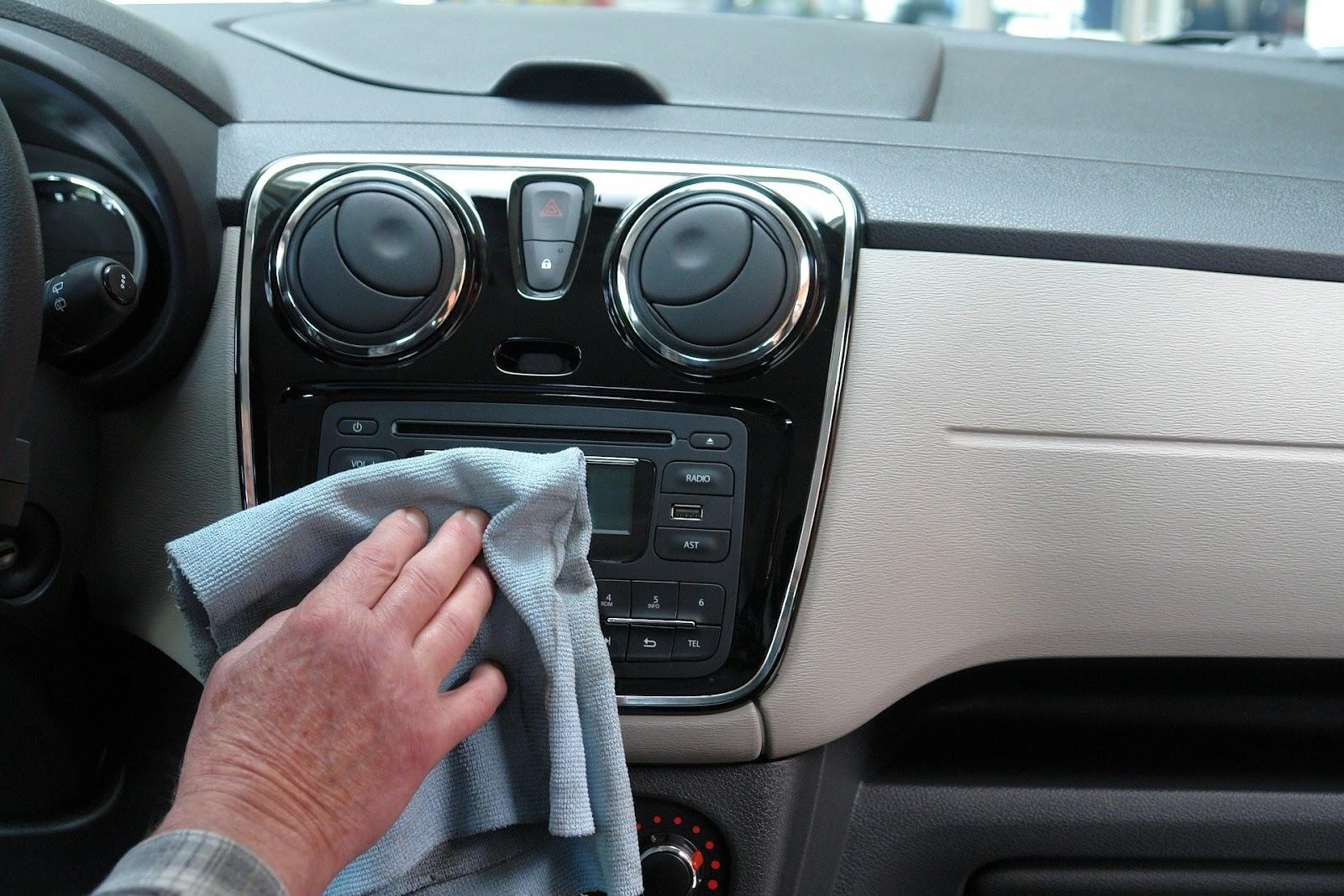 Uma mão limpando um rádio de um carro com uma toalha.