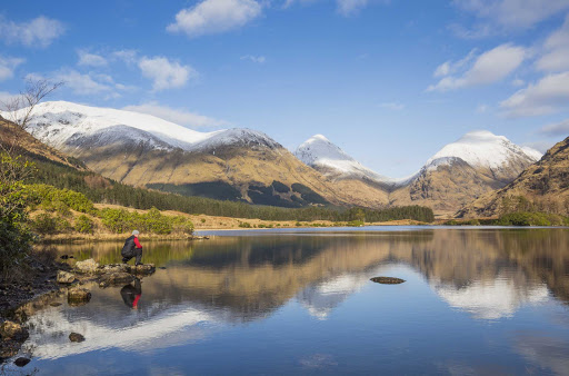 Lochan Urr in Glen Etive with a snow-capped Buachaille Etive Beag and Buachaille Etive Mor in the background in western Scotland.