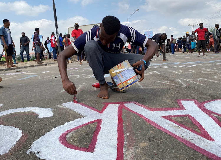 A demonstrator paints 'End Sars', referring to the Special Anti-Robbery Squad, on a street during a protest demanding police reform in Lagos, Nigeria, on October 20 2020.