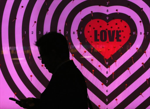A man using his mobile phone walks past a shop window with signs advertising the upcoming Valentine's Day, at a luxury store in Tokyo, Japan, last month. Picture: REUTERS
