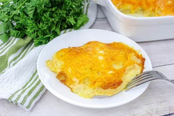 A Serving Of Super Cheesy Au Gratin Potatoes On A Plate.