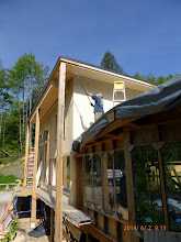 Photo: We'd preped the S. & W. cedar w/ UV-protective stain before installation.  Here our neighbor, John Haynes, works on the E. wall & the eaves.