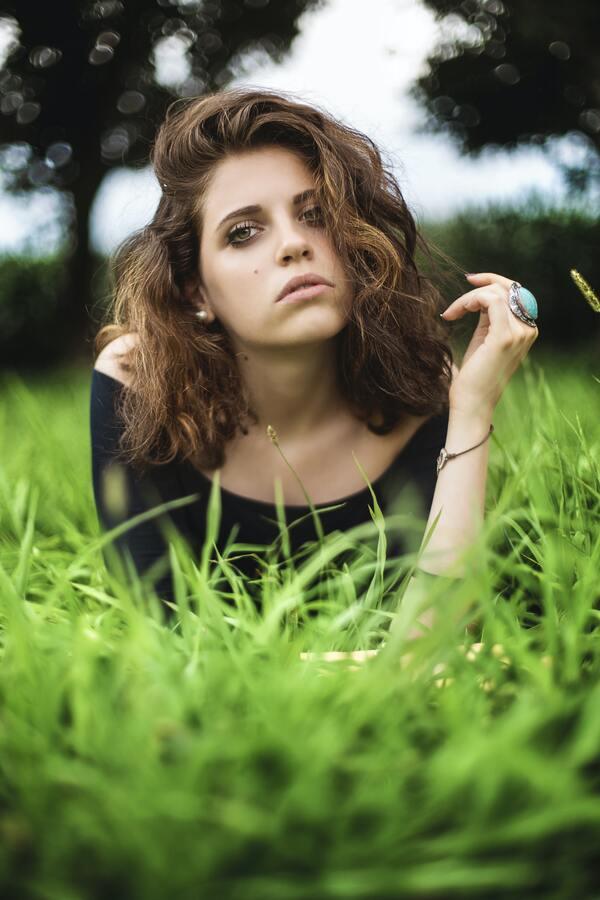 mulher morena posando deitada na grama