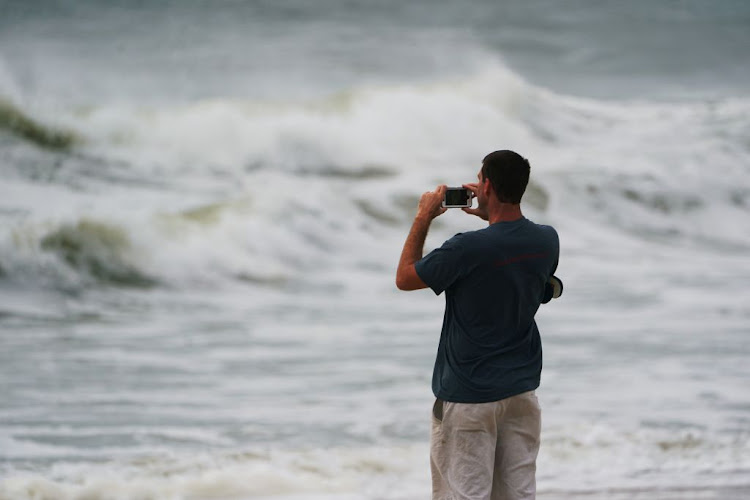A man takes photos of the sea swells before Hurricane Florence comes ashore on Carolina Beach, North Carolina, on September 13 2018.