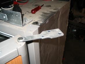 Photo: Coloco la puerta del congelador sobre la doble visagra y atornillo la visagra superior.