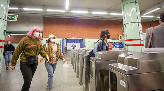 Varias personas pasan por los tornos de salida del Metro.