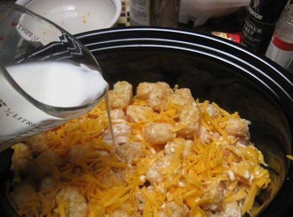 In a large lightly greased crockpot layer half of the tater tots then half...