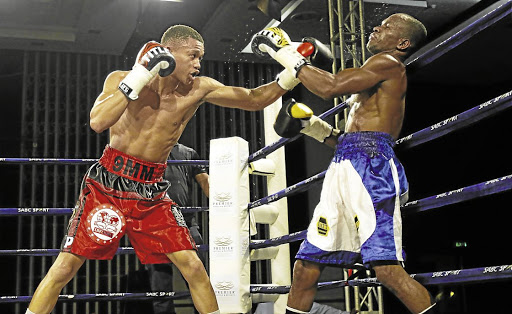 Ludumo Lamati pins Luis Mendeles of Colombia against the ropes on his way to winning the     then vacant IBF intercontinental  junior featherweight  title fight in  East London.