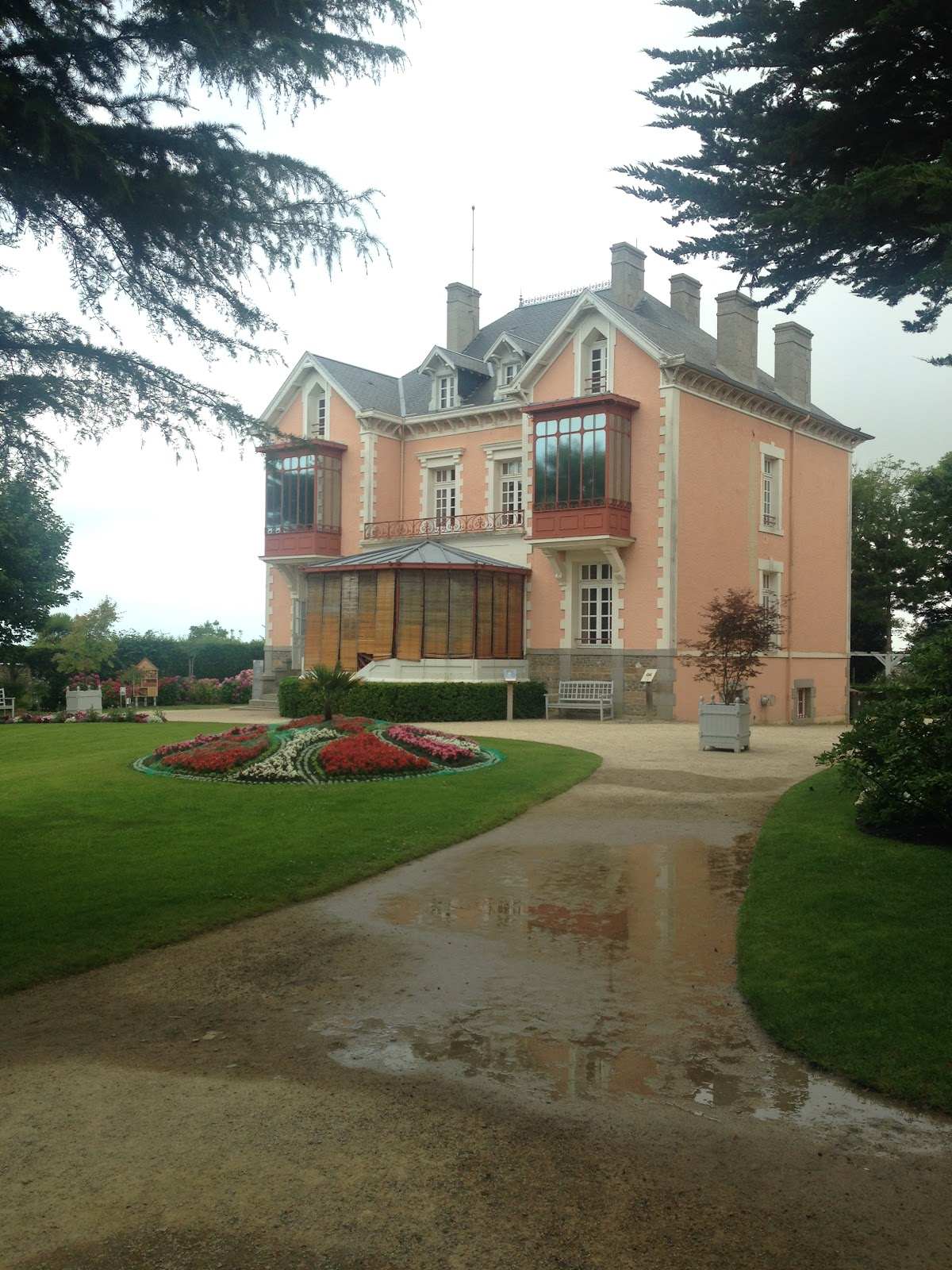 the childhood home of christian dior that has been turned into a dior museum in granville france. traditional home, neat lawn and no tourists. Photographed after rain.