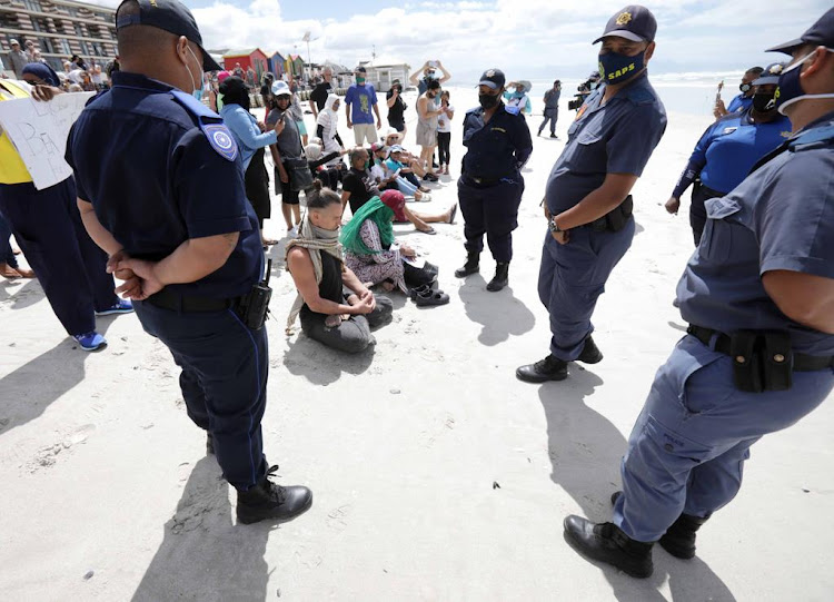 Yoga poses and prayer thwarted public order police during a lockdown beach ban protest at Muizenberg on January 30 2021.