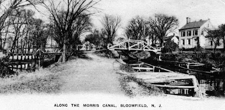 Photo: Postcard photo on the tow path of the Morris Canal at the bottom of Inclined Plane 11 East. McNair homestead on the right, Collins House center. Bridges are Baldwin Street - left is over Third River, right is over the Morris Canal. Historical Society of Bloomfield.