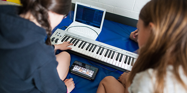 Two girls using a keyboard and computer