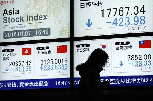 A pedestrian walks past an electronic stock board displaying the Nikkei 225 Stock Average and the Shanghai Stock Exchange Composite Index in Tokyo, Japan. Picture: BLOOMBERG/TOMOHIRO OHSUMI