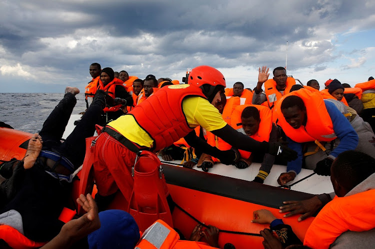 Panicking migrants try to reach a rescue craft from their overcrowded raft in the central Mediterranean Sea. Picture: REUTERS/Yannis Behrakis