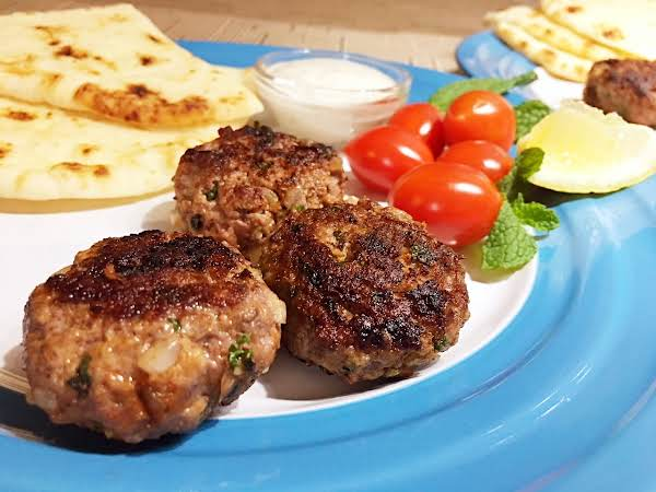 Meat Patties And Cherry Tomatoes On A Blue Plate With Flatbread And Sauce In A Small Bowl In The Background.