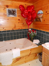 Photo: A jacuzzi bath for two in woodsmoke.  There is a separate shower in this bathroom too! This is set with balloons and roses - add separately or with the romance package.