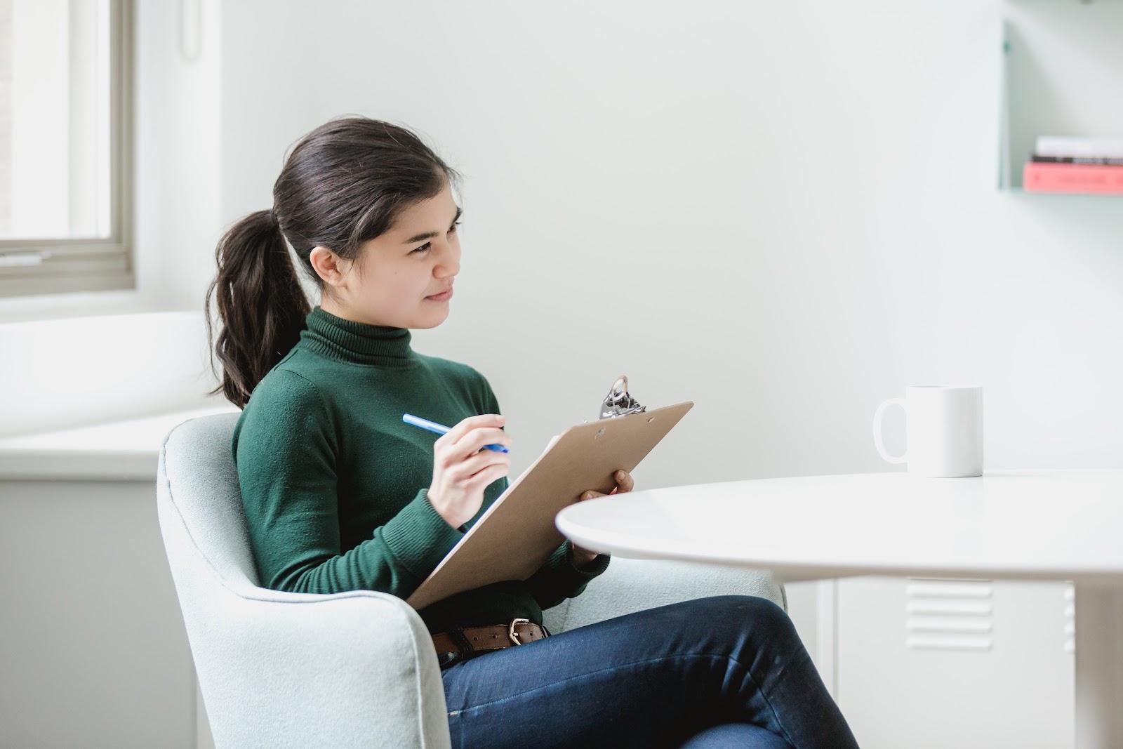 Uma mulher com uma caderneta avaliando alguém.
