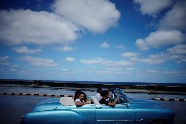 Tourists ride in a vintage car at the seafront in Havana, Cuba.