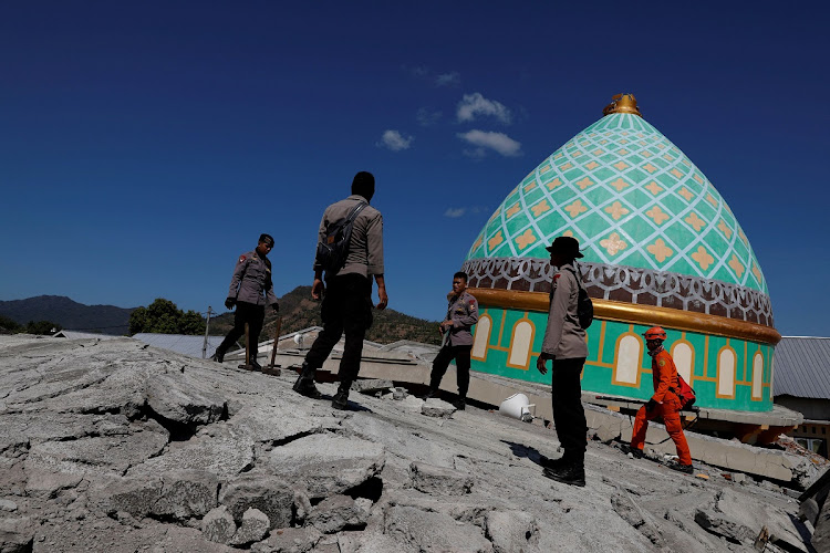 Rescuers and policemen walk on top of a collapsed mosque as they try to find survivors after an earthquake hit on Sunday in Pemenang, Lombok Island, Indonesia, on August 7, 2018. Picture: REUTERS/BEAWIHARTA