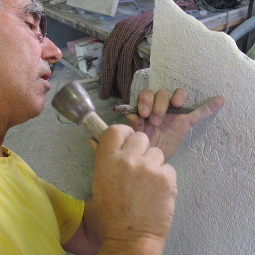 gravure lapidaire traditionnelle au ciseau et à la massette  de lettres sur une stèle funéraire en pierre naturelle