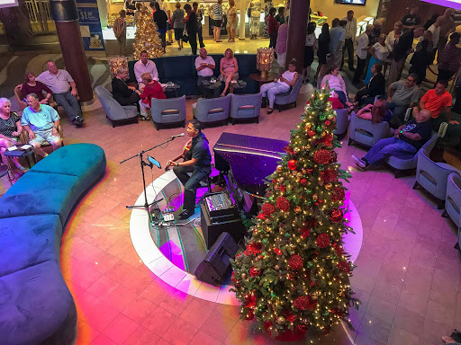 A guitarist performs during the Christmas holidays in the atrium of Norwegian Jade.
