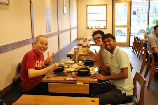 Dnyan, Kyehyun, and his father smile and throw up peace signs over a shared meal.