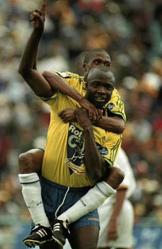 Sundowns' Roger Feutmba celebrates scoring in the Rothmans Cup final against Chiefs at FNB Stadium 20 years ago, with Fire Masilela on his back. Chiefs won on penalties. /PAUL VELASCO