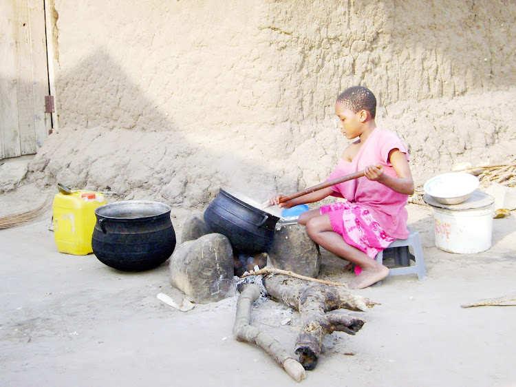 A girl cooks with firewood.