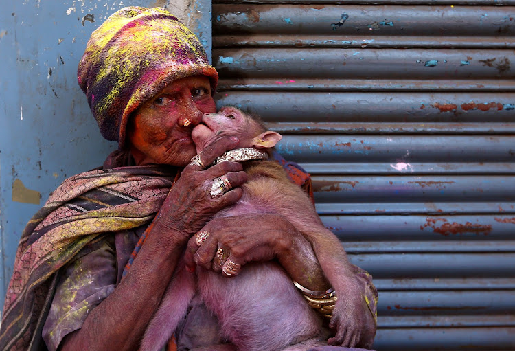 A woman daubed in colours kisses her monkey during Holi celebrations in Chennai, India.
