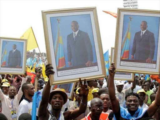 Supporters of Congolese President Joseph Kabila carry his portrait during a pro-government rally in DRC capital Kinshasa, /REUTERS